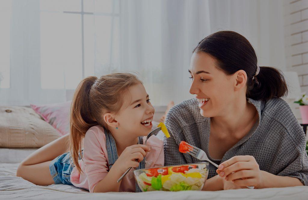 Madre e hija tomando una ensalada de verano